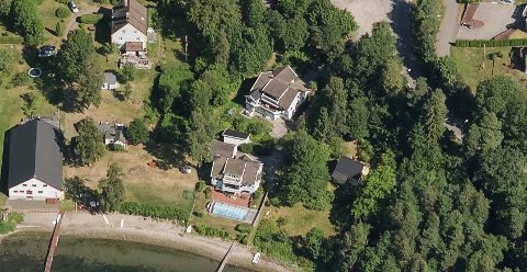 Eiendommen midt i bildet, med basseng og brygge, er adressen det søkes om støttemur på.