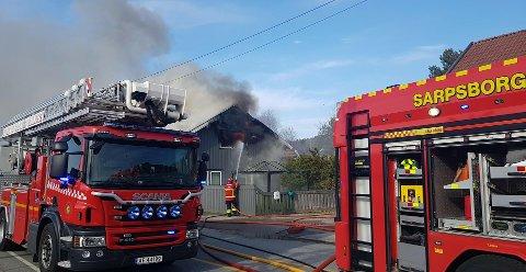 Mannskaper fra Sarspborg brannvesen jobbet iherdig for å slå ned flammene som stakk ut fra andre etasje i huset.
