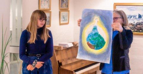 Frida Elen (12) under prisutdelingen, mens Grete Skrede fra Lions Ås/Eika presenterer vinnerbildet fra Åsgård skole.