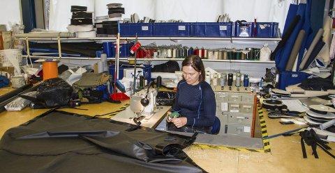 BRUKER GOLVET: Liv Monika Storsæt står i ein arbeidsstasjon nedsenka i golvet. Dermed har ho heile golvet som sybord. Her er ho i aksjon med å sy ein presenning bestilt av Forsvaret.
