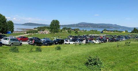 Bilene står parkert overalt ved Midtsandtangen. På stranda er flere hundre personer samlet.