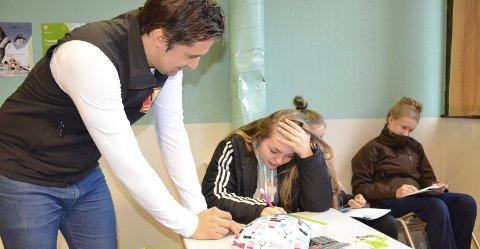 Lærer økonomi: Kristine Fornes forsøker å løse budsjettoppgaven hun har fått. Ungdomsøkonom Da Rudi Abrahamsen i Helgeland Sparebank hjelper til.  Foto: Ann Kristin Kjærnli