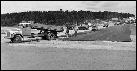 1977: Parkeringsplassen ved Tunevannet får asfalt på seg. På det 43 år gamle bildet ser det ut for at det er grus fra før av. En gammel og god Volvo snutebil leverer asfalt. Huset som ligger i svingen i Tunevannsveien er nå borte. Journalist Håkon Aurlien bodde der i mange år. Nå er det revet og erstattet av flere leiligheter. Fortetning heter det. Firkantede «bokser» er satt opp som boliger. Parkeringsplassen er ofte full av biler, for Tunevannet og områdene rundt, er et populært utfartssted. Sarpsborg kommune har vært flinke til å tilrettelegge for det.