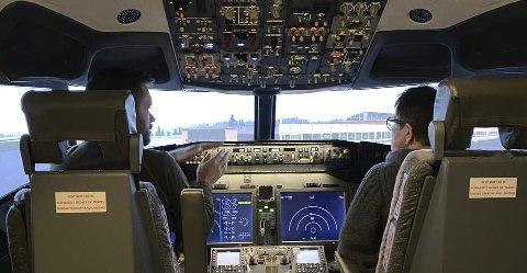 Trygg flytur: Pilot Jan Roger Ekedal har her med seg sin mor, Tulla, i flysimulatoren. Hun er ikke veldog glad i å fly, men denne reisen likte hun.