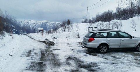 Skorsteinen fra branntomta stikker opp bak til høyre. I forgrunnen er parkeringsplassen til Guvåghytta.
