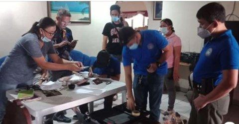RANSAKER: Politi og etterforskere fra et sentralt kriminalavsnitt CIDF ransaket huset nordmannen leide i Dumaguete på Filipinene.  42.-åringen sitter sammen med den pågrepne 22 år gamle kvinnen i sofaen bak tjenestemennene.