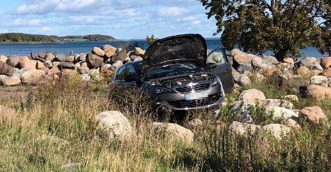 En bil har havnet i en steinrøys.