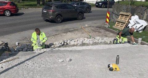 10.000 STEINER: To håndverkere var i full gang med å lege de siste kvadratmeterne med stein foran den nye krika mandag.