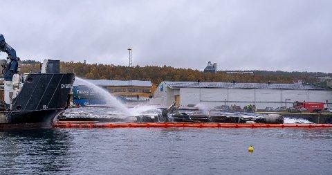 ARBEIDER ENDA: Torsdag ettermiddag foregår det enda slukningsarbeid etter brannen i tråleren. Den 64 meter lange tråleren kantret ved kai i Breivika torsdag formiddag.