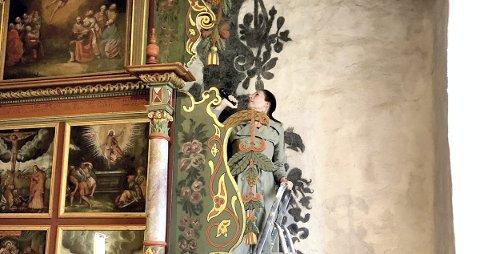 UNDERSØKELSER: Elisabeth Andersen fra NIKU undersøker veggen bak altertavla i Hof kirke. Finnes det spor av endringer? Foto:  Susanne Kaun