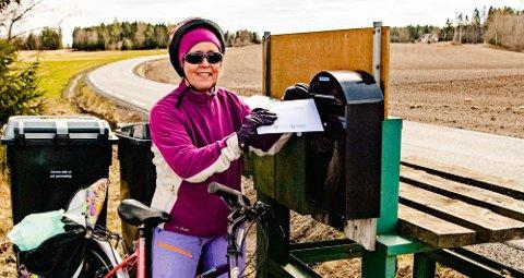 DELER UT KART: Gunnhild Baugerud har syklet seg en tur helt til Bakk lengst syd i Kroer og vært postbud for den nye spesialutgaven av Ås ILs turkart fra 2018. Her er hun klar til å legge kart i postkassene ved Gåvim og Østby i Kroerveien.