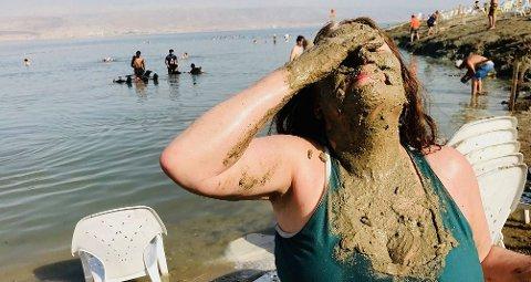 NYTER FERIEN: Brenda fra USA smører seg inn med lere ved Dødehavets bredd i Israel.