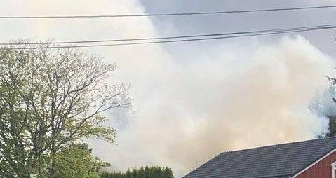 KRAFTIG RØYK: Det brant kraftig i huset da nødetatene kom fram. Brannen er i huset som ligger bak taket på bildet.