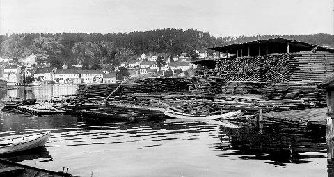 Trelastlager på Øya: Dette fotografiet et tatt først på 1920-tallet. Kikker man litt på bakgrunnen kan man se at Blindtarmen ikke er påbegynt. Det spesielle med bildet er det store trelastlageret som da lå på Vestre Øya. Hit kom skutene og båtene for å hente trelast, for igjen å få fraktet dette videre ut i verden. I våre dager kan man fortsatt se rester i sjøen hvor trelasten ble lagret.