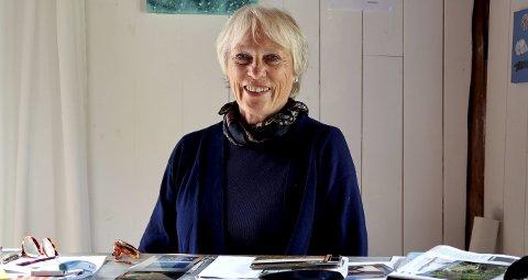 Kari Gjertsen Trythall ved skrivebordet. Der har hun oversikt over alt som skjer og ser hvem som trenger hjelp og kanskje vil kjøpe et bilde.