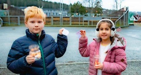 Einar (8) og Leah Marie (8) var med å gikk i Luciatoget sammen med resten av tredjetrinnets elever, med sine lysende lykter. Her står de to midt på skoleplassens «øy» hvor det er hengt opp mange lapper med ønsker om fremtidshåp.