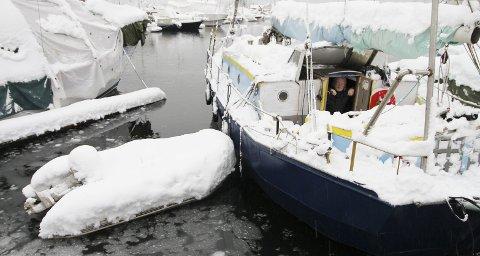 Han drar ikke ut med gummibåten i dag: – Jeg har fått tatt det verste, sier båteieren, og titter ut på snøen som har begynt å gå over til sludd og regn. Det betyr mye tyngde på mange båter i havna. Alle foto: Pål Nordby