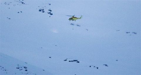 NYTT SØK: UNNs ambulansehelikopter flyr over området der mottakeren som henger under helikopteret fanget opp signaler fra skredsøkerne 4. januar. Første fase i operasjonen, som starter i neste uke, er å bruke helikopteret på ny for å prøve å få en mer nøyaktig stedsangivelse på funnet 4. januar. Foto: Ola Solvang