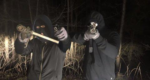 GANGSTERRAP: To maskerte menn skyter med det som ser ut som skarpladde automatvåpen i videoen til Doni Mula.