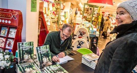 Guri Woxholtt kjøper skogbok og forfatter Lars Sandven Dalen signerer.