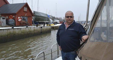 HJEMME OG JOBB: Fra boligbåten sin kan Frode Johnsen se rett bort på marinaen han har overtatt i bakgrunnen. Han har mange planer for utvikling av driften. Foto: Marianne Holøien