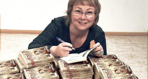 NY RUNDE: Serien Storgårdsfolk skrevet av Eva Stensrud ble på 60 bøker. Trolig avsluttes Skyggespill før, smiler hun, og signerer de første 500 bøkene. FOto: Tomas Algard
