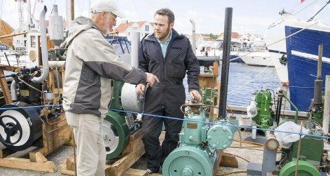 GÅR SOM EI KLOKKE: Alf Berdinessen forteller om Skude-motoren som sto i farens båt, til Hans Inge Østhus, medlem i Råseglarlaget. – Det er første gang jeg ser den helt ferdig restaurert, sier Berdinessen. Foto: Ruth Sunnanå Sveistrup