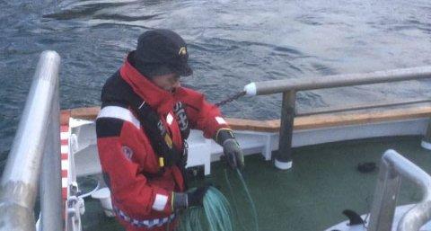 REDNING: Maskinist Niels Heinemann gjør klar til å berge surferen som ligger i vannet. Foto: Runar Iversen