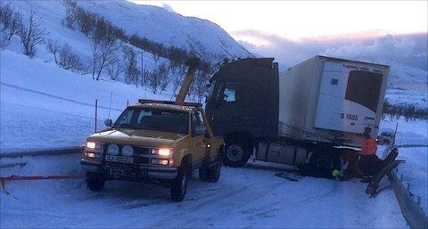 Den vesle bergingsbilen er surret fast til autovernet med ei jekkestropp. Slik forsøkte man å få løs vogntoget som er lastet med 25 tonn fisk. Flere bygder er isolert etter trailerhavariet. Foto: Rune Richardsen