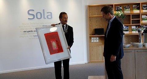 Ordfører Håkon Rege (h) donerer et trykk til banksjef Kjetil Bru i SR-bank før han foretar den offsielle virutelle snorklippingen.