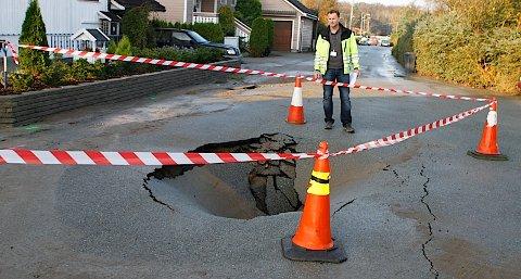 Arne Sandvik i avdeling for kommunal teknikk ser på hullet der vannet sprengte seg gjennom i Fjordveien på Joa.