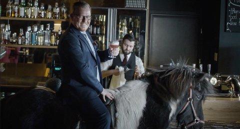 """SCENE: På slutten av reklamen får vi hotelldirektør Erik Taraldsen """"on a horse""""."""