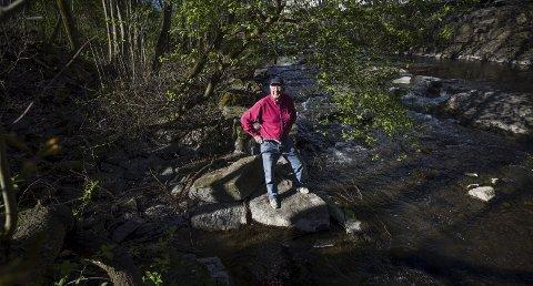 FØRSTE STEIN: Steinar Bunæs på den første steinen de fant som del av den 20 meter lange grunnmuren til saga far 1600-tallet. Foto: Lisbeth Lund Andresen