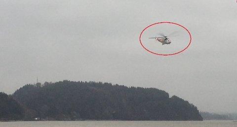 SIRKLER: Et redningshelikopter sirkler over Glengshølen i Sarpsborg i området rundt Ravneberget fredag ettermiddag.