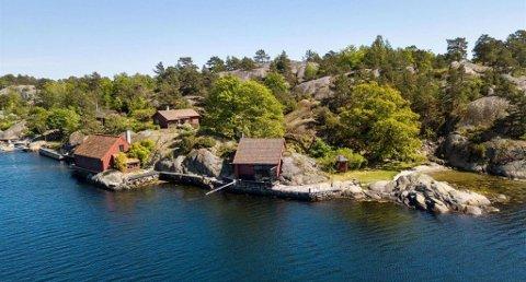 Hytta ligger bakerst i bildet. Til venstre er det et båthus, mens bygningen til høyre er en badstu. Foto: DNB Eiendom