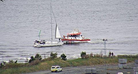 Her får seilbåten bistand fra redningsskøyta. På land venter politiet.