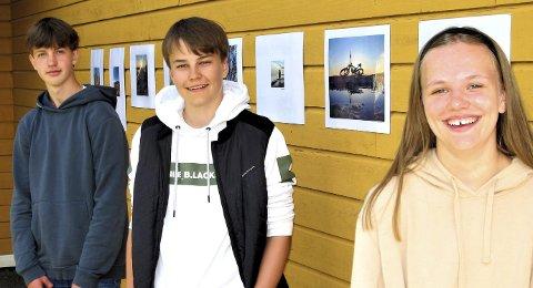 TRE FOTOKUNSTNERE: Fra venstre ser vi Magnus Eik, Andreas Fjeldstad og Juliane Josefsen. På veggen ser vi et utvalg av bildene som ble produsert i hjemmeperioden.