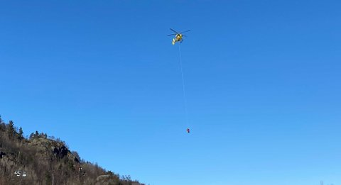 Her blir turgåeren fraktet ned fra fjellet hengende under luftambulansen.