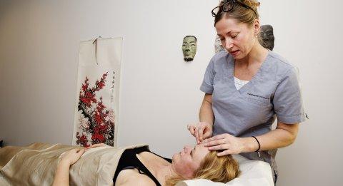 HELSE I HVERT STIKK: Her setter akupunktør Elisabeth Kongsrud nåler på pollenallergiker Anette Røsjorde.Alle foto: Silje Rindal