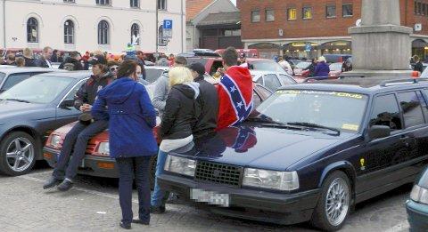 SØRSTATSFLAGGET: Dette bildet viser en mann som står drapert i sørstatsflagget på Torget i Halden skjærtorsdag for noen år siden. Ordfører Anne-Kari Holm mener dette flagget bør pakkes ned for godt .Arkivfoto