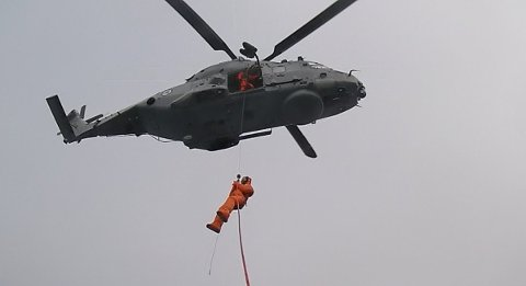 HEISES OPP: Her blir det syke besetningsmedlemmet fra den norske tråleren heist opp i NH90-helikopteret. Vedkommende ble fløyet til sykehuset i Hammerfest.
