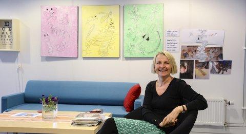 Varmosletta: Seksjonsleder for Familietjenesten i Avdeling for barn og familier, Berit Nonskar, forteller at elevene har tatt utgangspunkt i områder de besøker, som Varmosletta i bildene bak henne, i kunsten sin. Foto: Lisa Ditlefsen