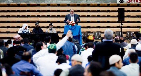 Ole Jacob Flæten idet han holder tale under eid-feiringen i Skedsmohallen nylig. Ifølge Avisen Dagen sitter Fahad Qureshi, leder for Islam Net, til høyre ved bordet i bakgrunnen.