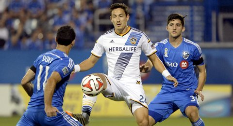 Sep 10, 2014; Montreal, Quebec, CAN; Los Angeles Galaxy midfielder Stefan Ishizaki (24) plays the ball as Montreal Impact midfielder Dilly Duka (11) defends with teammate Eric Miller (3) during the first half at Stade Saputo. Mandatory Credit: Eric Bolte-USA TODAY Sports