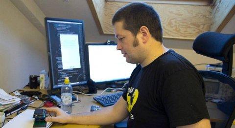 Her demonstrerer Jon Helge Nistad korleis ein «dings» kan lade trådlaust. Under skriveblokka er ein sendar, og trådlaus lading kan vere framtida – i staden for tradisjonell lading via USB og liknande. FOTO: SOLVEIG NESJE PEERSEN