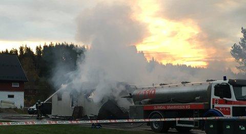 ETTERSLOKKING: Brannvesenet holder vakt og driver med etterslokking på branntomta. Politiets krimteknikere vil undersøke brannstedet så snart det er mulig.