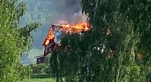 STOR BRANN: Det brant kraftig i en låve som brant helt ned til grunnen i løpet av kort tid. Brannmannskaper jobber med å sikre andre bygg på eiendommen.