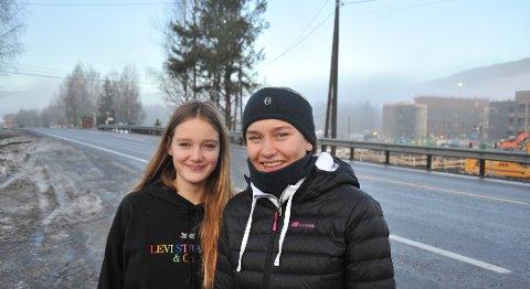 KRYSSINGSPUNKT:Tuva Mitacek (15) og Amalie Stovner Hovlid (15) omtrent der det snart kommer gangfelt, mens det bygges nytt kryss og ny undergang til Elvetangen. Bak til høyre ser vi konturene av den nye barneskolen i Hakadal.