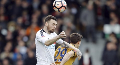 Tottenham Hotspur's Harry Winks, rear, and Fulham's Kevin McDonald challenge for the ball during the English FA Cup soccer match between Fulham and Tottenham Hotspur at Craven Cottage stadium in London, Sunday, Feb. 19, 2017.(AP Photo/Frank Augstein)