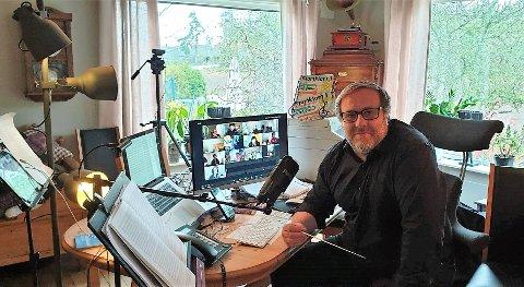 DIRIGERER FRA STUA: Geir Aage Sveen dirigerer både Frydenlund og Slemmestad skolekorps hjemmefra der han har rigget til med lys, lyd og pc-skjermer for å følge med musikantene som spiller.